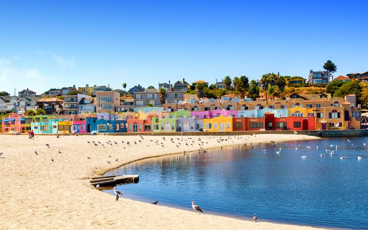 A colorful row of rainbow houses by the beach.