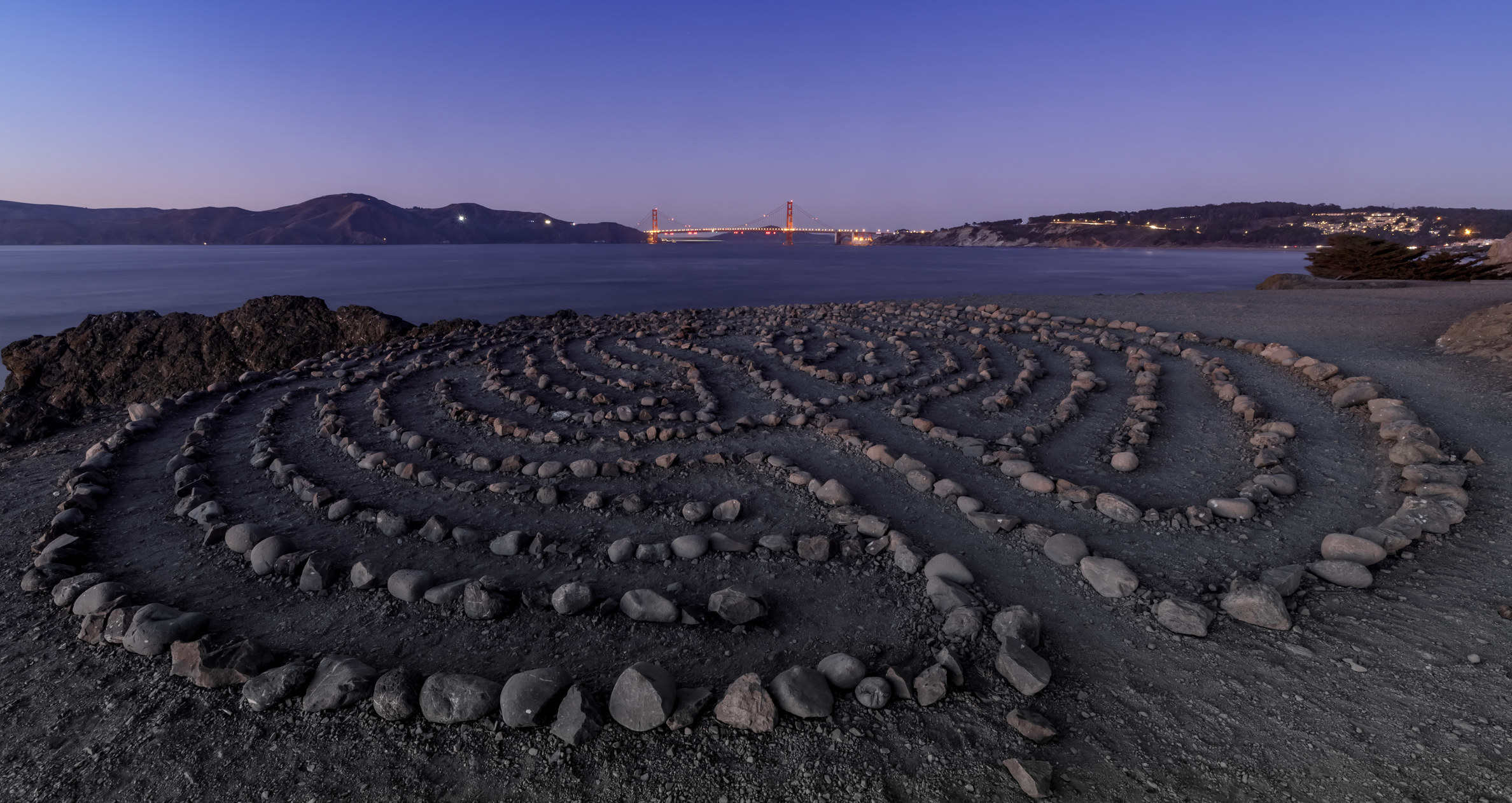 A rock maze overlooking an ocean and city view.