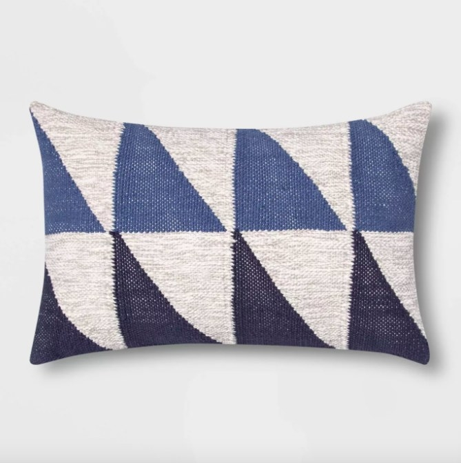 The pillow with a pattern of gray, blue, and navy blue triangles
