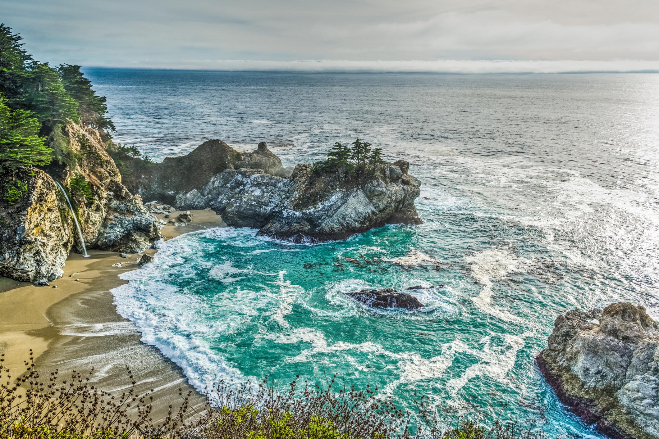 A bird's eye view of ocean water, sand a tall waterfall.