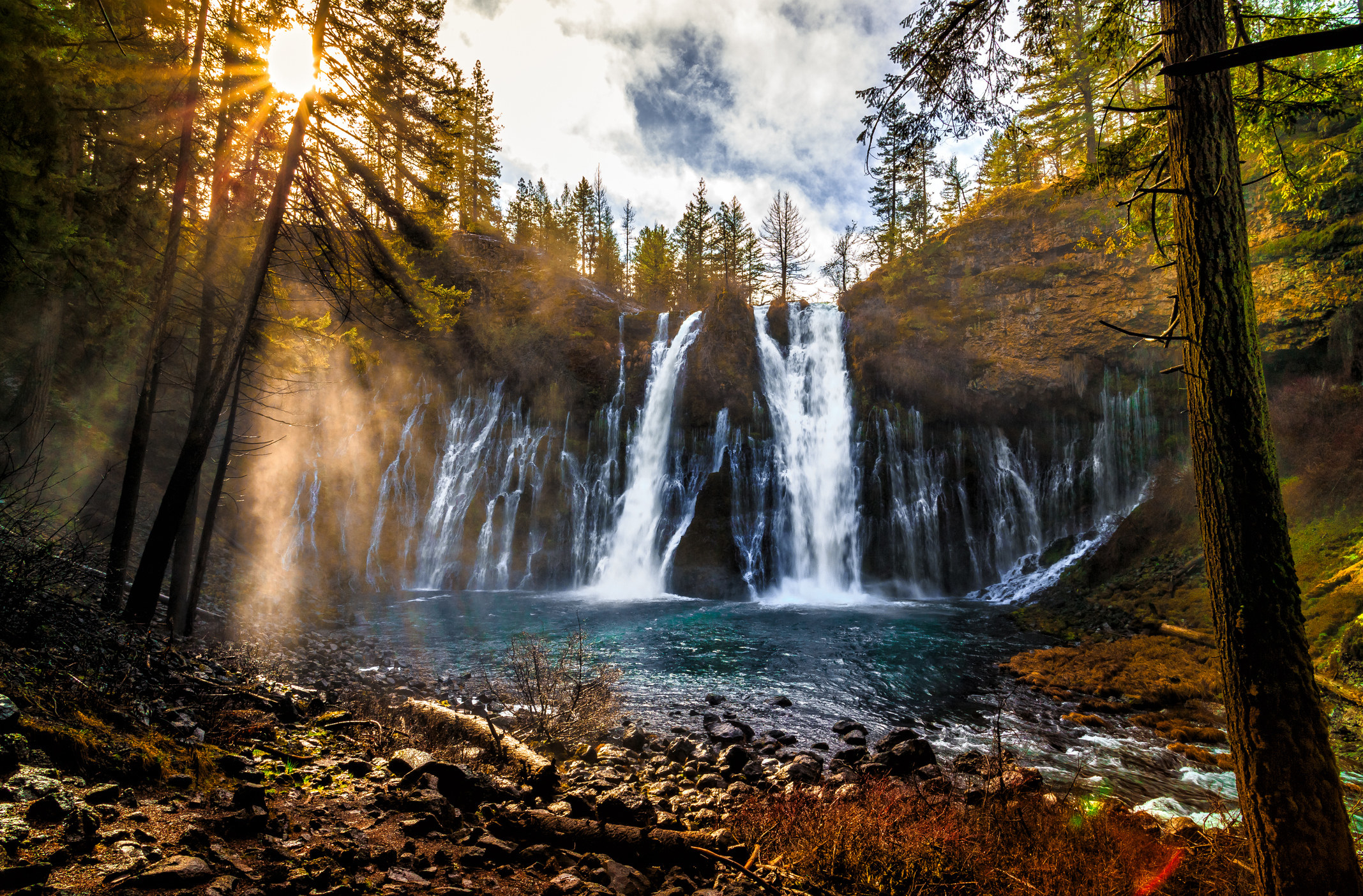 A cascading waterfall with the sun and trees nearby.
