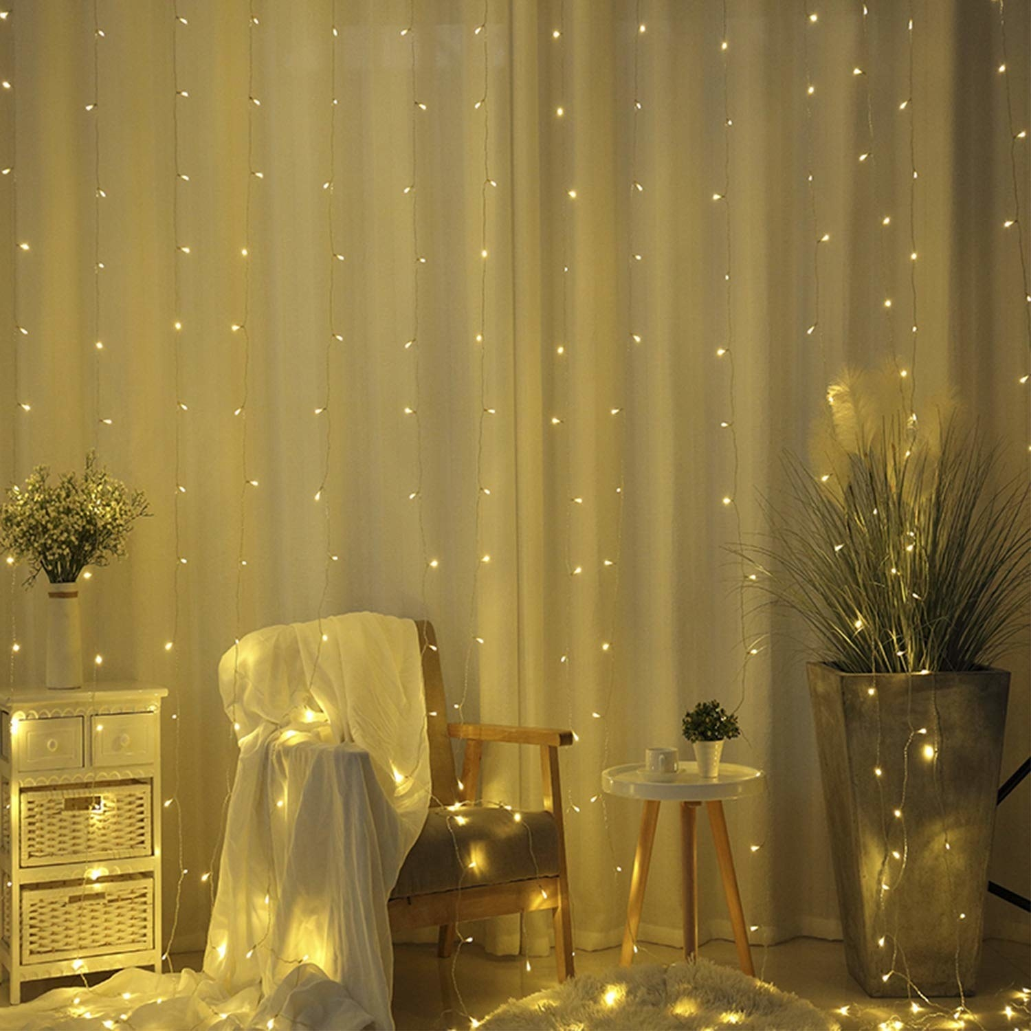 A lit up room with a plant, side tables, a chair, and curtains all covered with string lights.