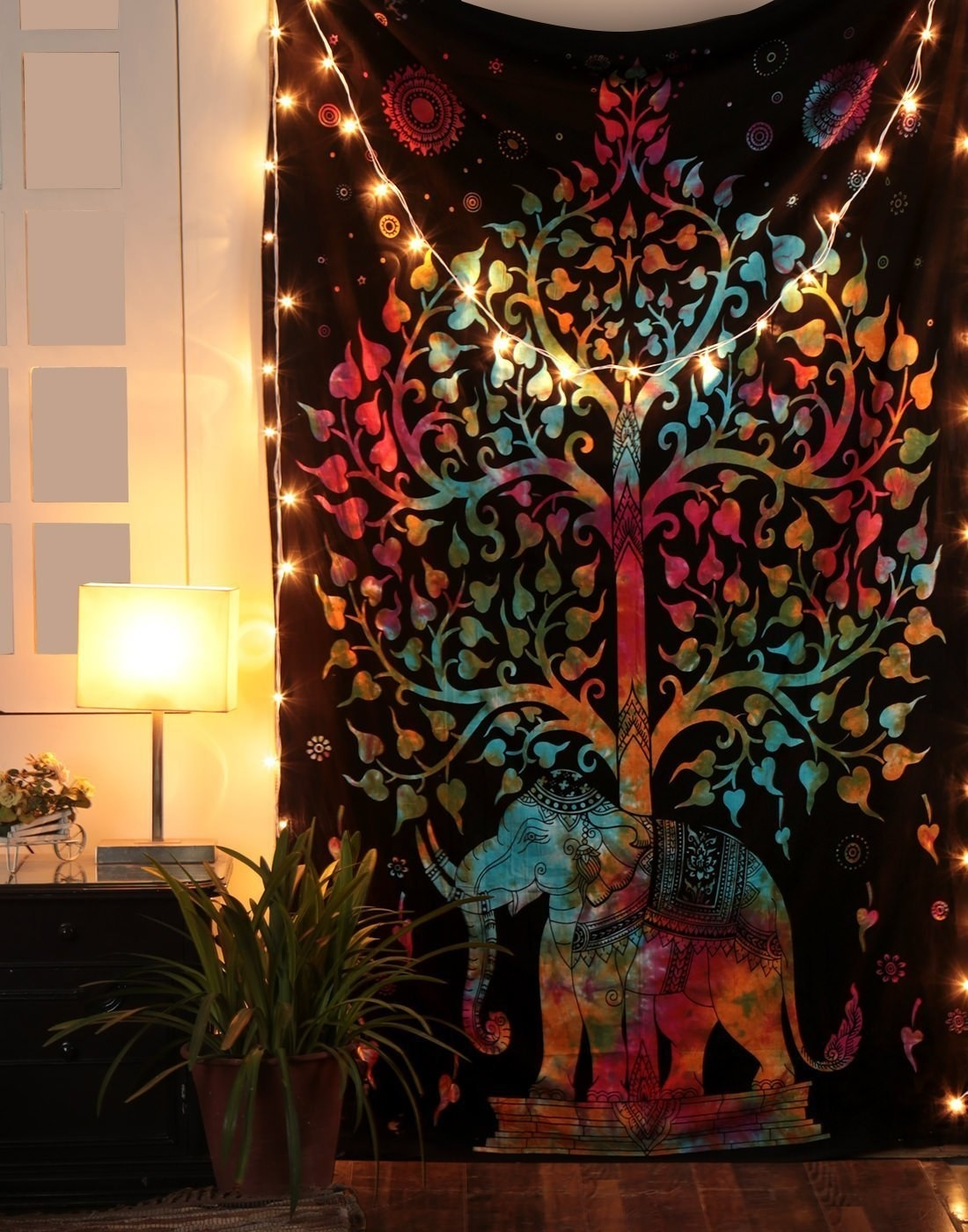 Tapestry with the design of an elephant and a tree, hanging on a wall with string lights decorating its corners.