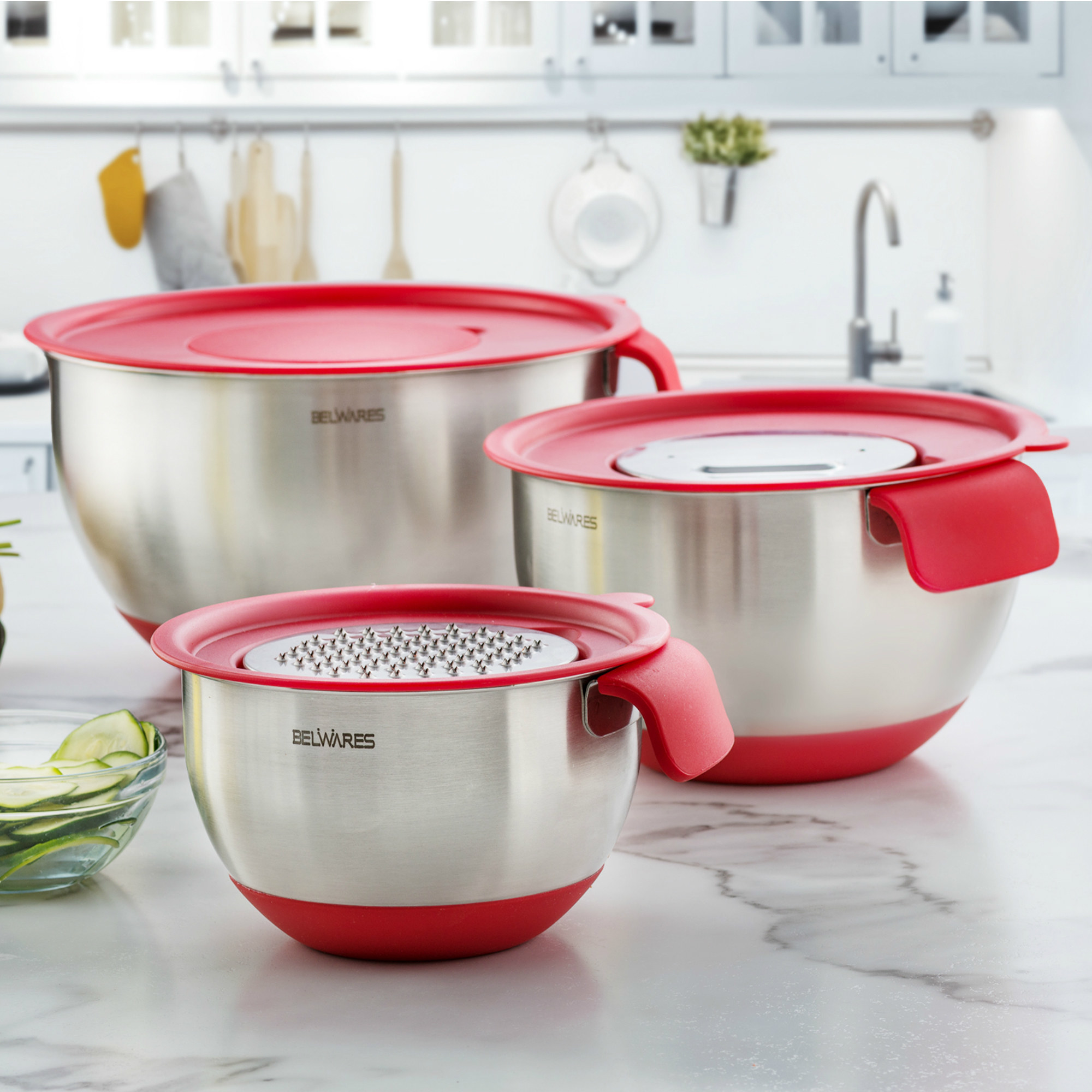 Set of three stainless steel bowls with red tops, including lid inserts for graters and slicers