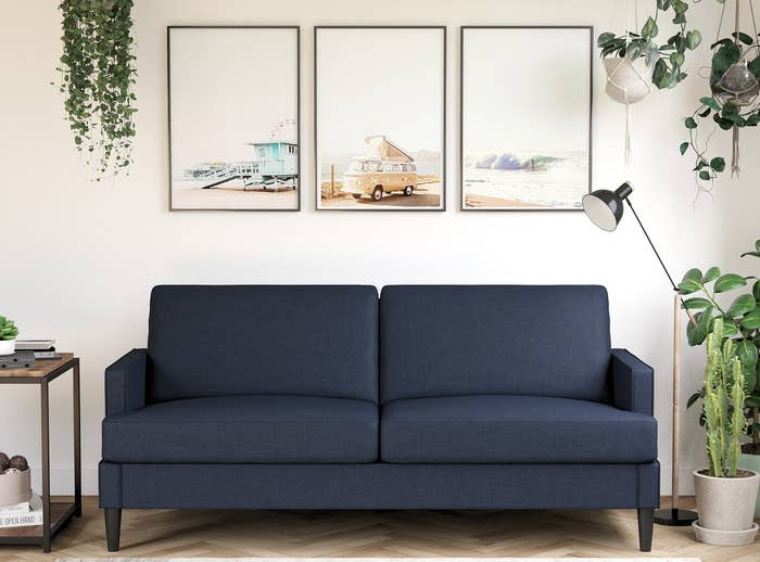 Blue sofa with rectangular arms and dark legs