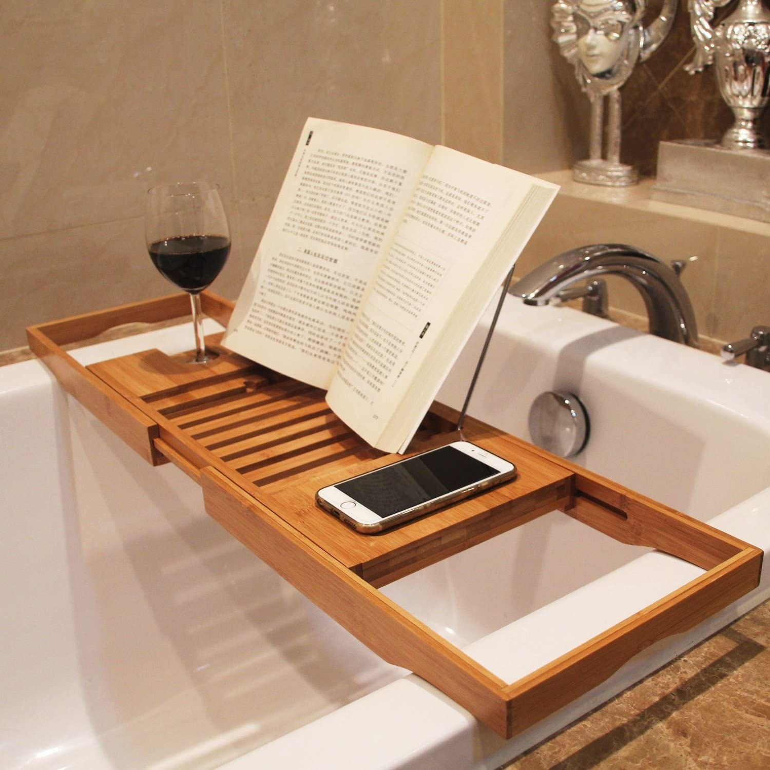 A bath caddy spread over a tub with a special spot for a wine glass a book being propped up and a phone