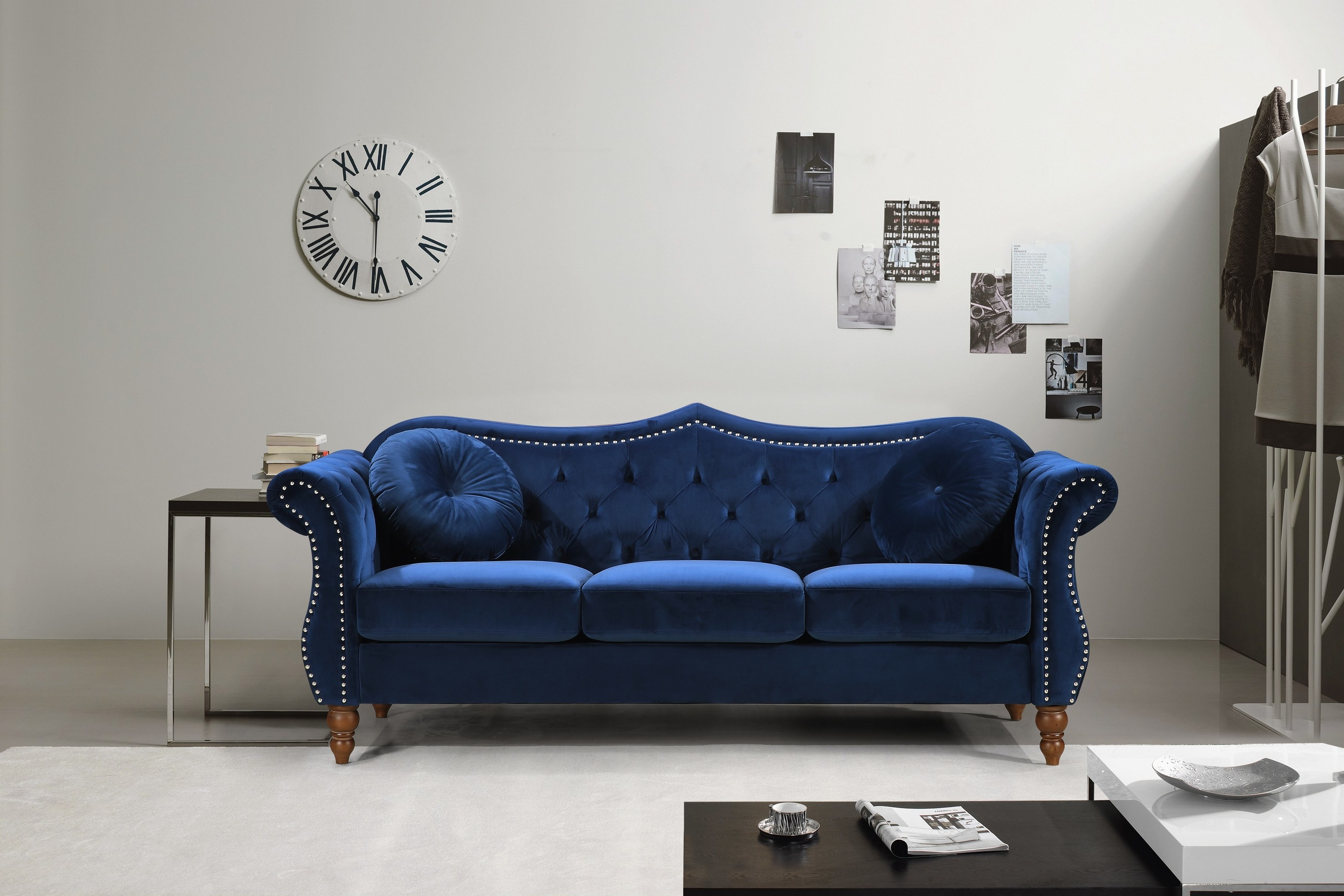 Blue tufted velvet sofa with studs and pointed backboard
