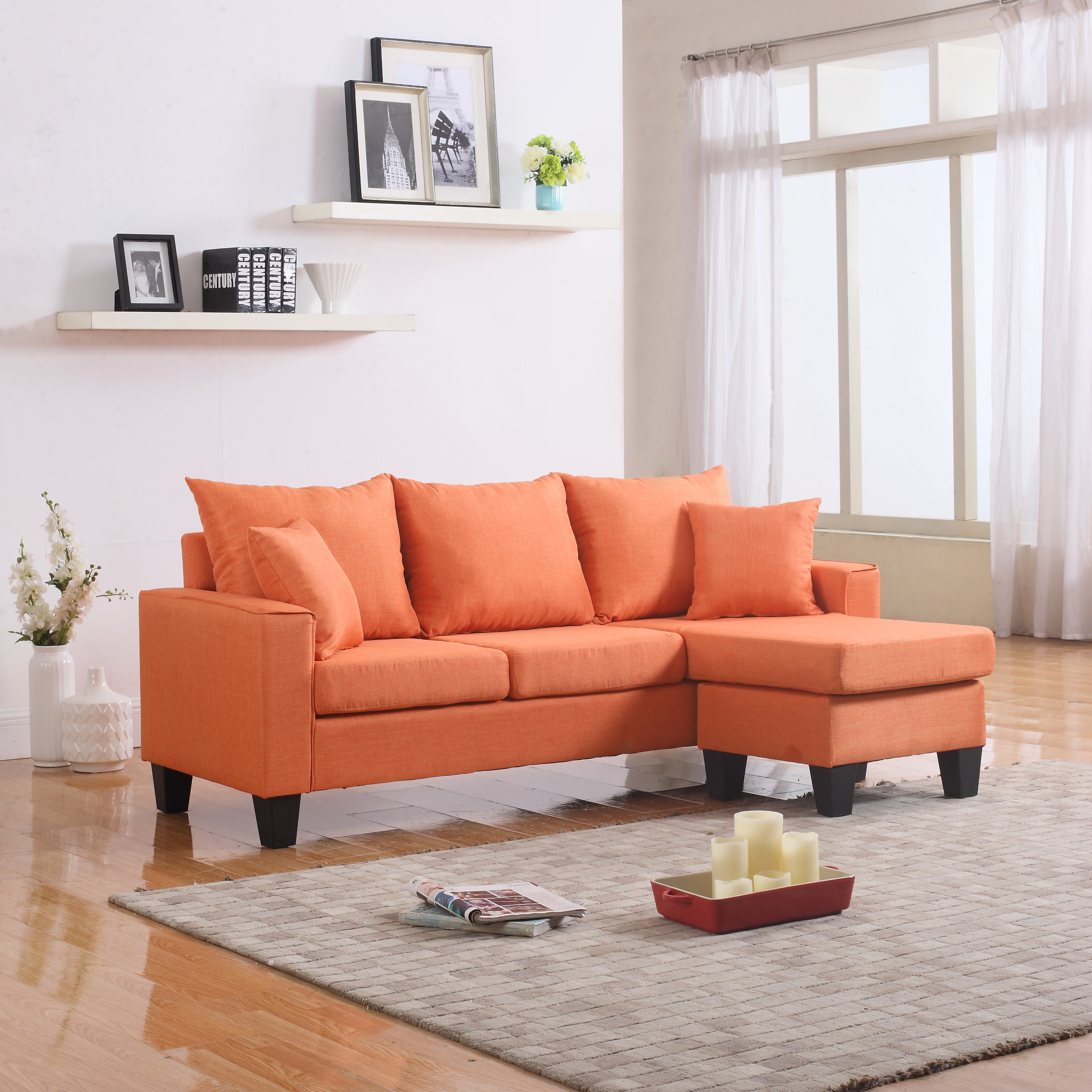 Orange couch with matching pillows and thick dark wooden legs