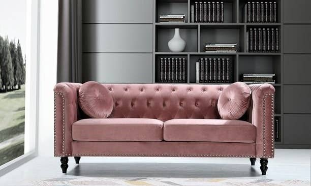 Tufted velvet couch with studs and dark wooden legs
