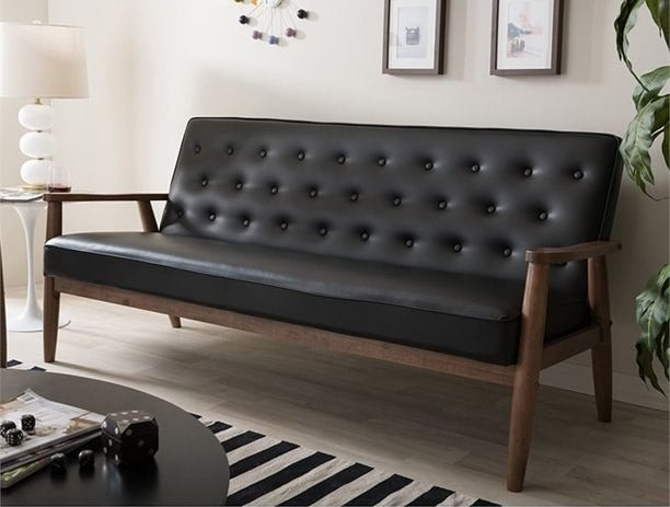 Black faux-leather tufted couch with wooden frame
