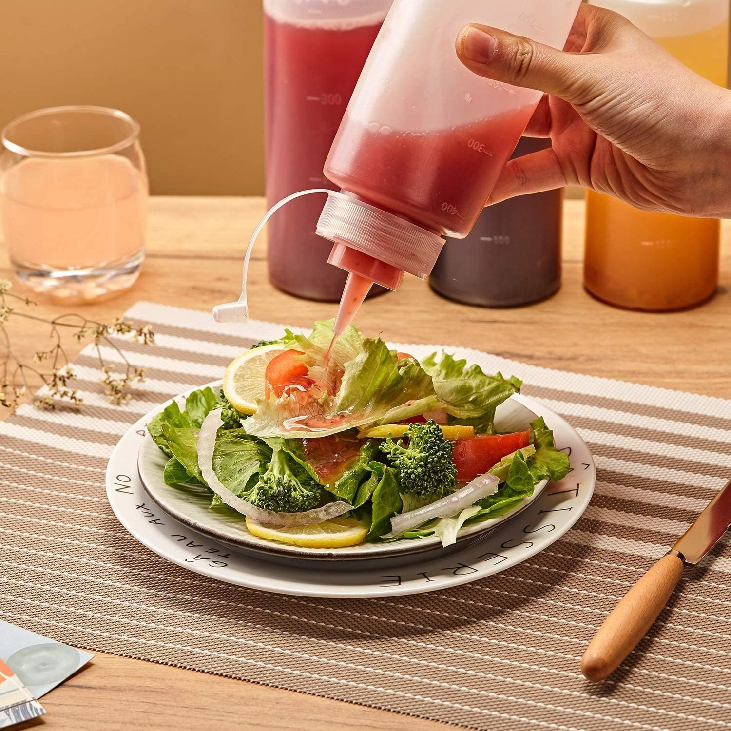 A squeeze bottle squeezes dressing onto a salad