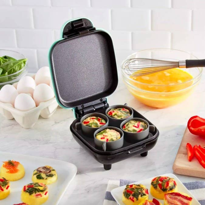 The opened egg bite maker, with four silicone cups inside holding the eggs