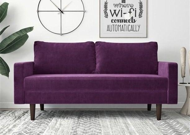 Purple velvet couch with dark wooden legs