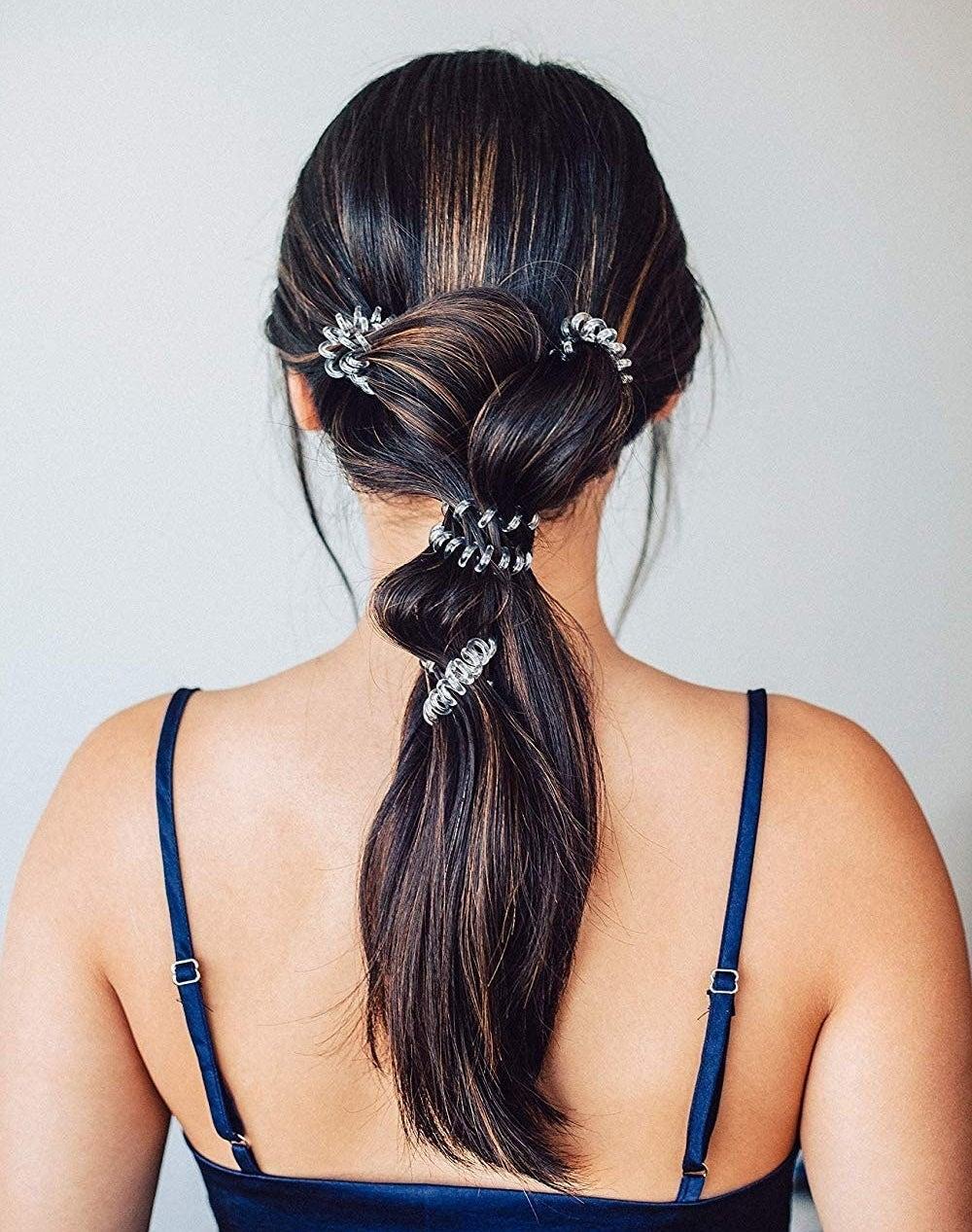 A person has multiple hair ties in their hair