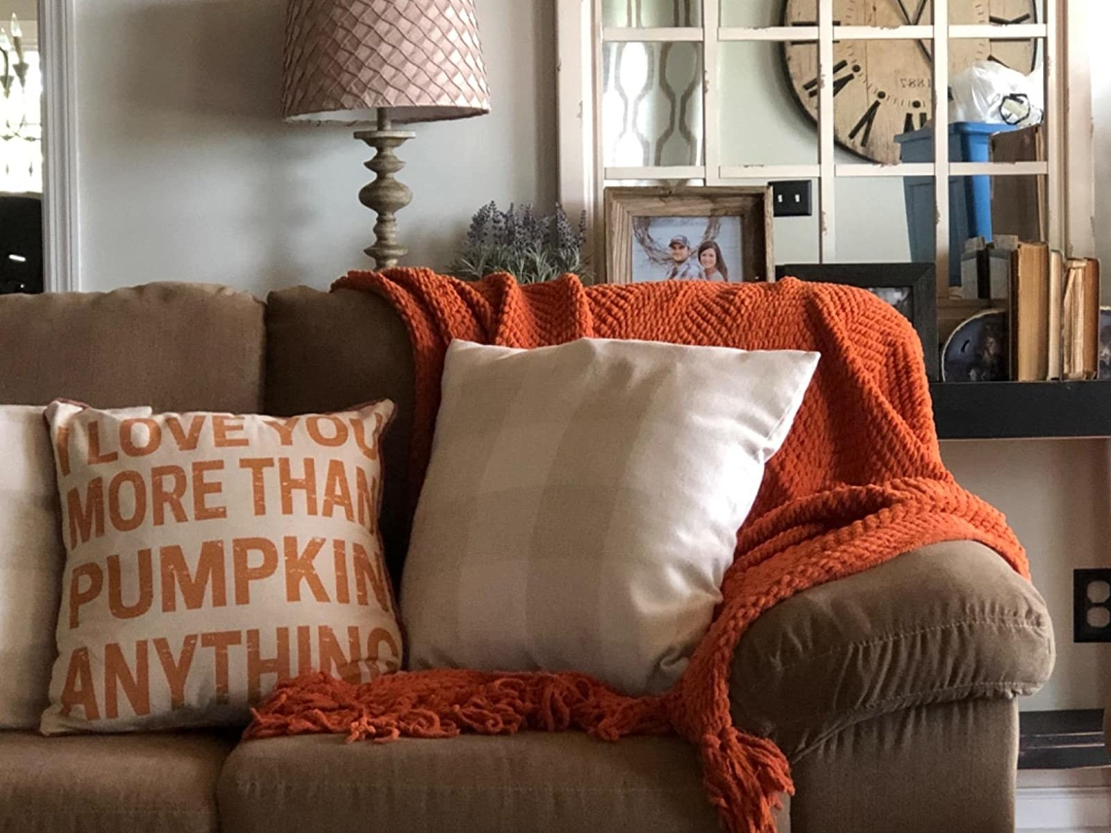 An orange throw blanket on the arm of a brown couch with some decorative pillows.