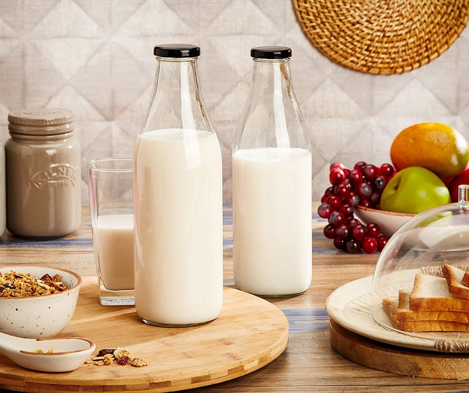 The glass bottles displayed with milk in them on a kitchen counter, surrounded by breakfast foods.