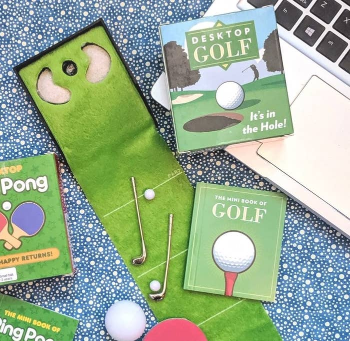 A mini golfing green with two clubs and two balls on it next to a computer