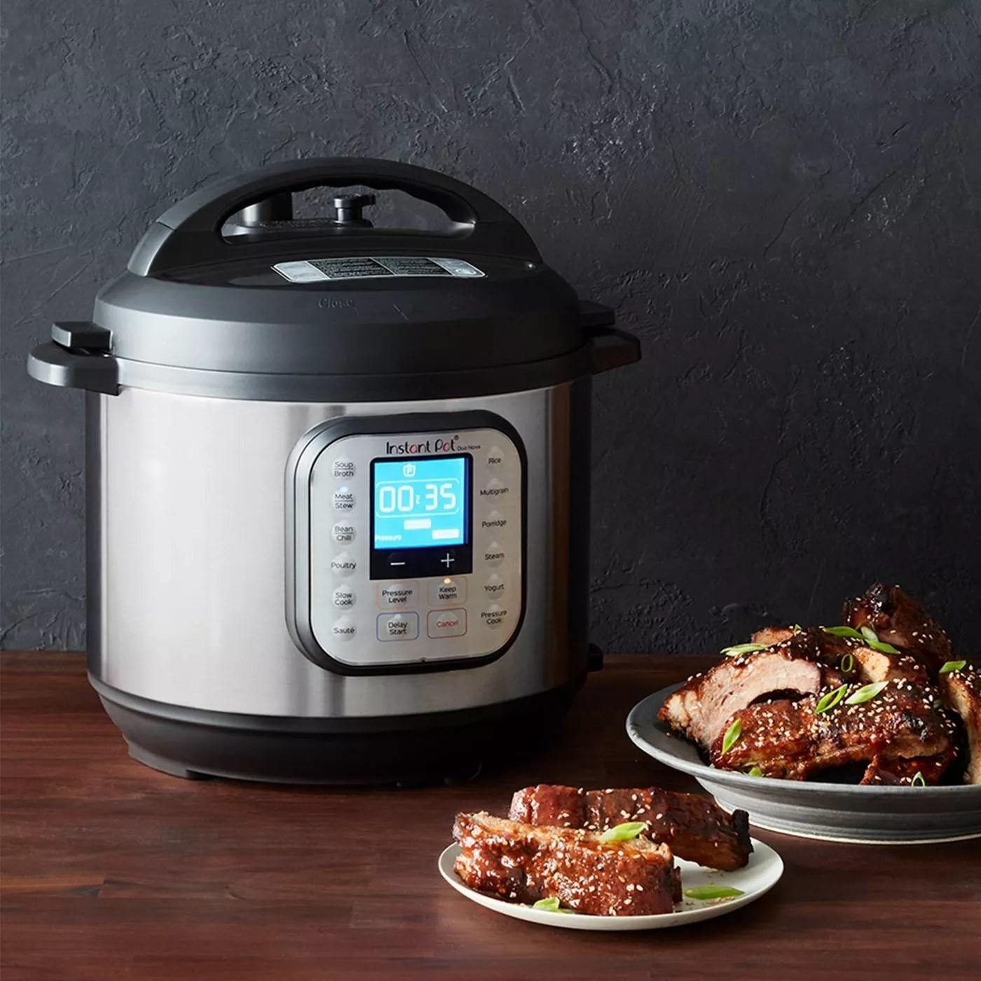 An Instant Pot next to plates of ribs