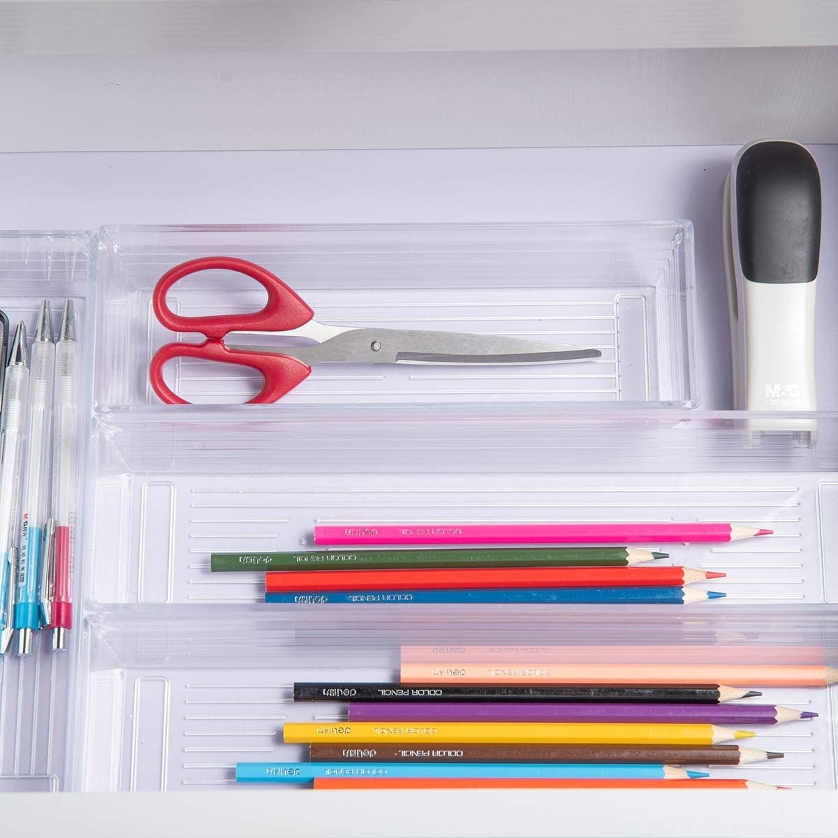 The acrylic trays in a drawer with pens, pencils, and scissors inside of them