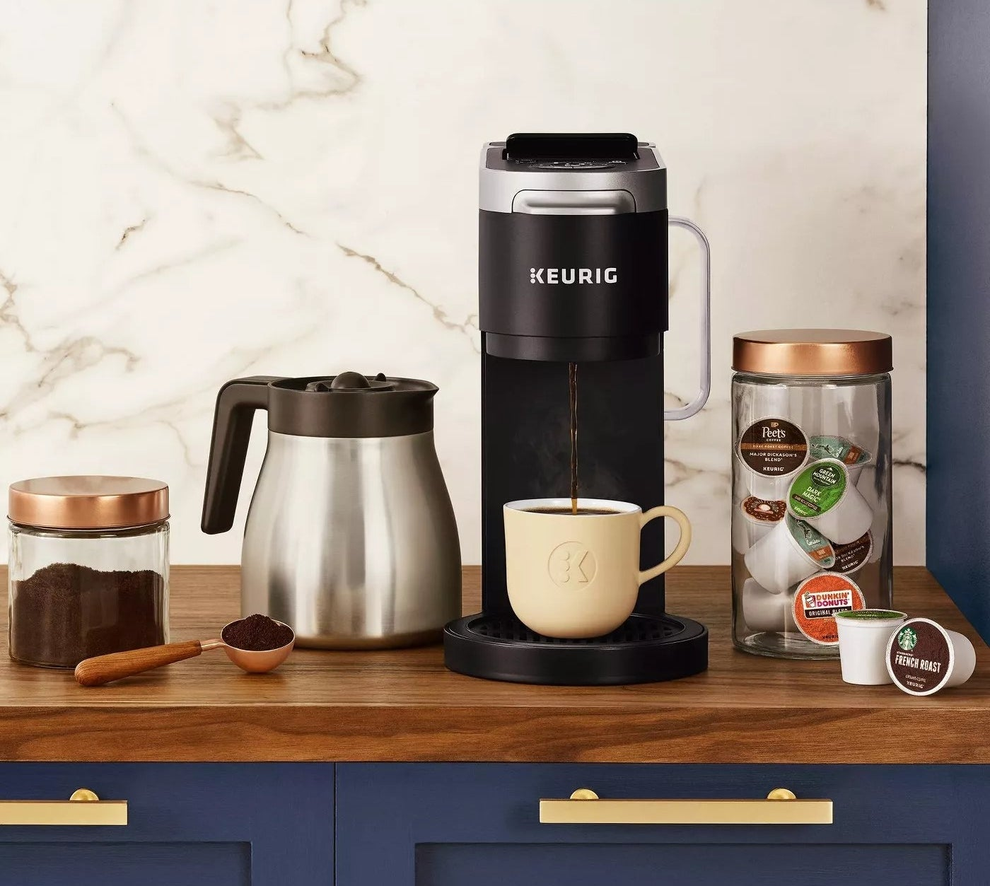 A Keurig machine making a cup of coffee next to its carafe and a jar of K-cups