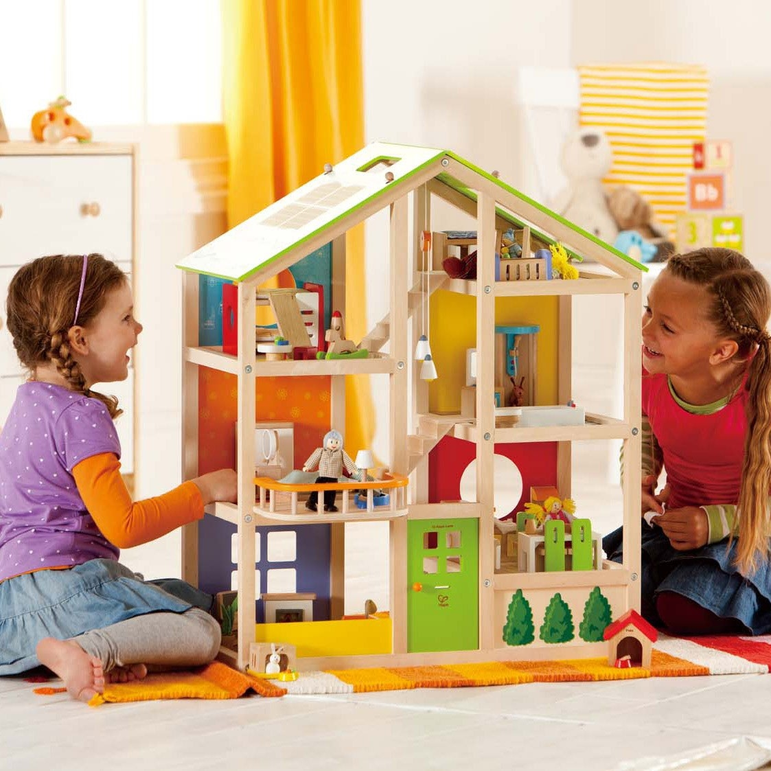 Two children playing with the dollhouse