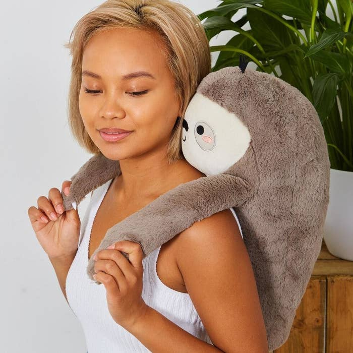 Model holding the large stuffed-animal-like sloth on their back and over their shoulders, like it's giving them a hug.