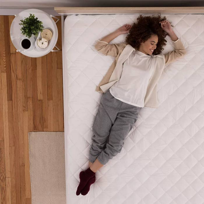 A model on a quilted mattress pad