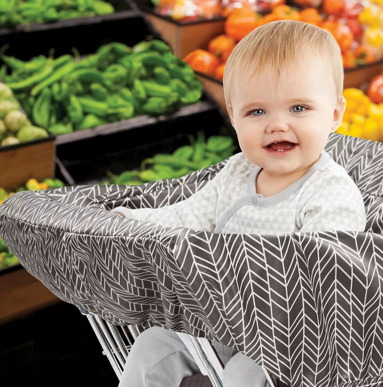 A baby in a shopping cart lined with a gray, padded cover