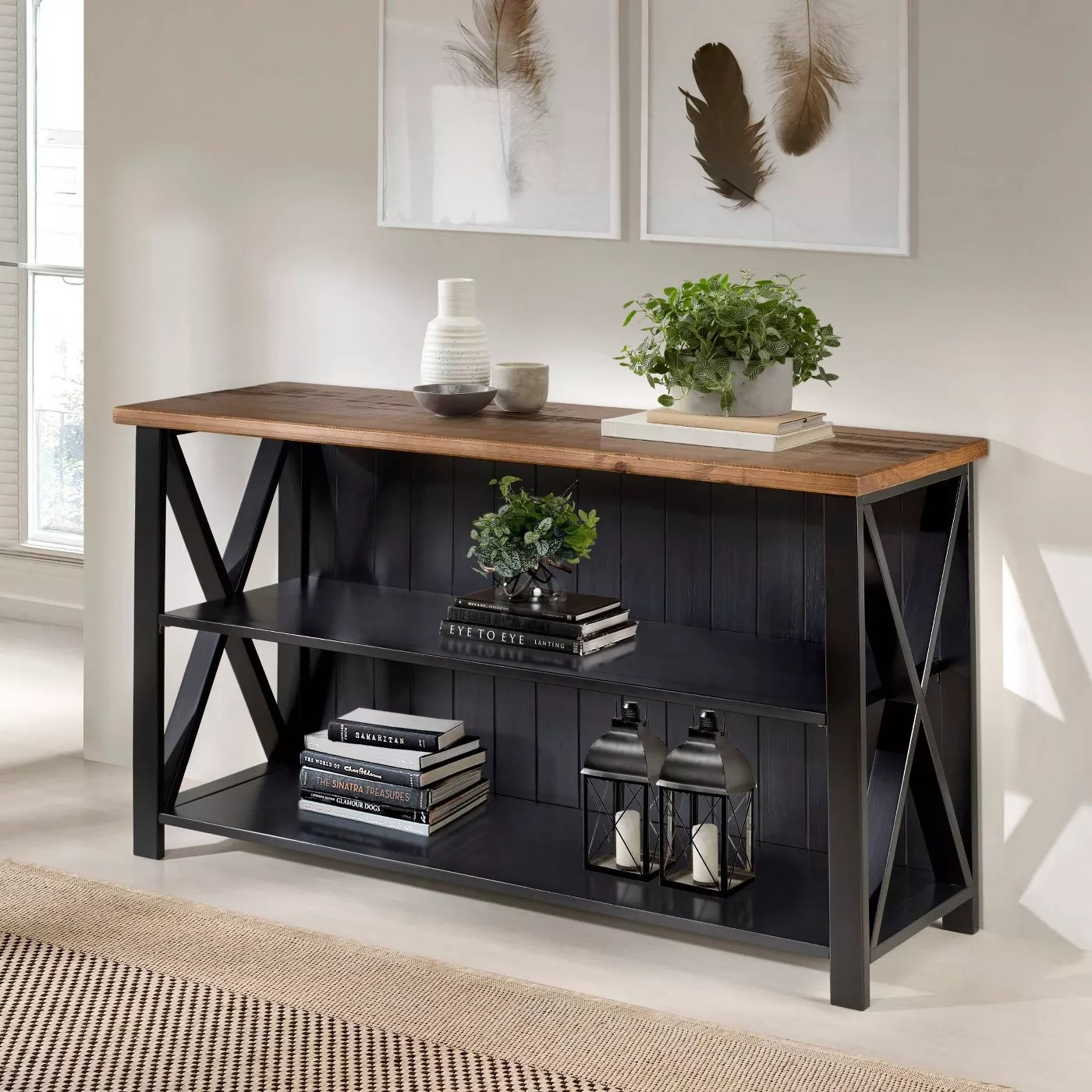 A black farmhouse console with a wood countertop and X-framed sides