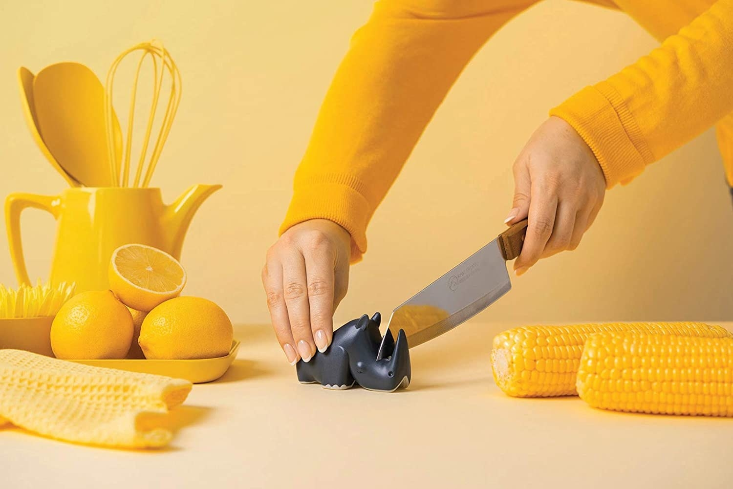 A person sharpens their knife on the rhino-shaped sharpener