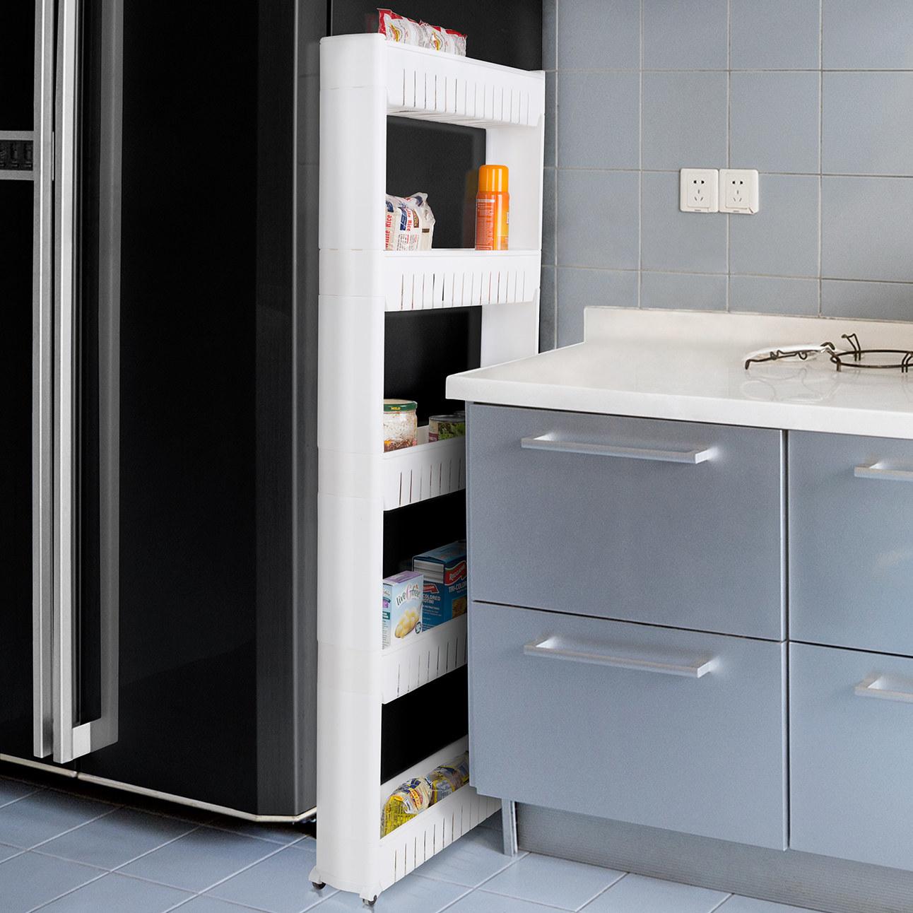 A skinny white plastic shelf next to a refrigerator