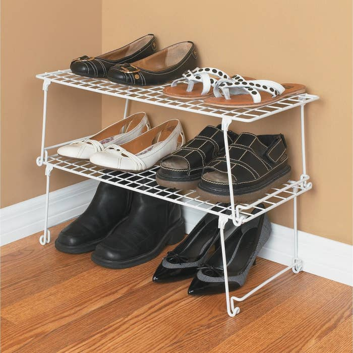 Six pairs of shoes on white stackable wire shelving