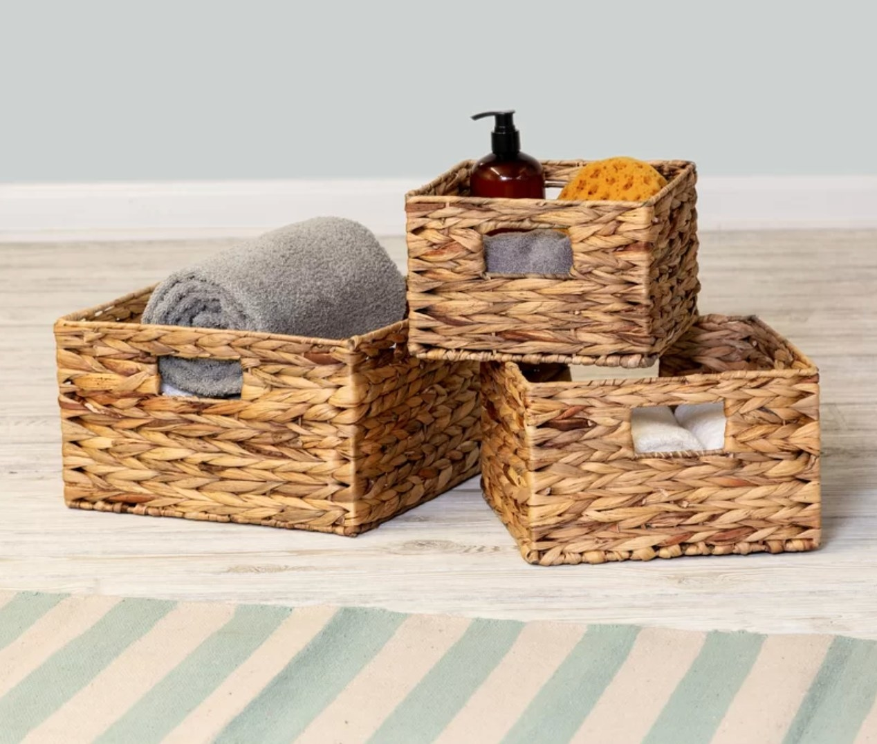The wicker baskets being used to hold bathroom items such as towel and loofah