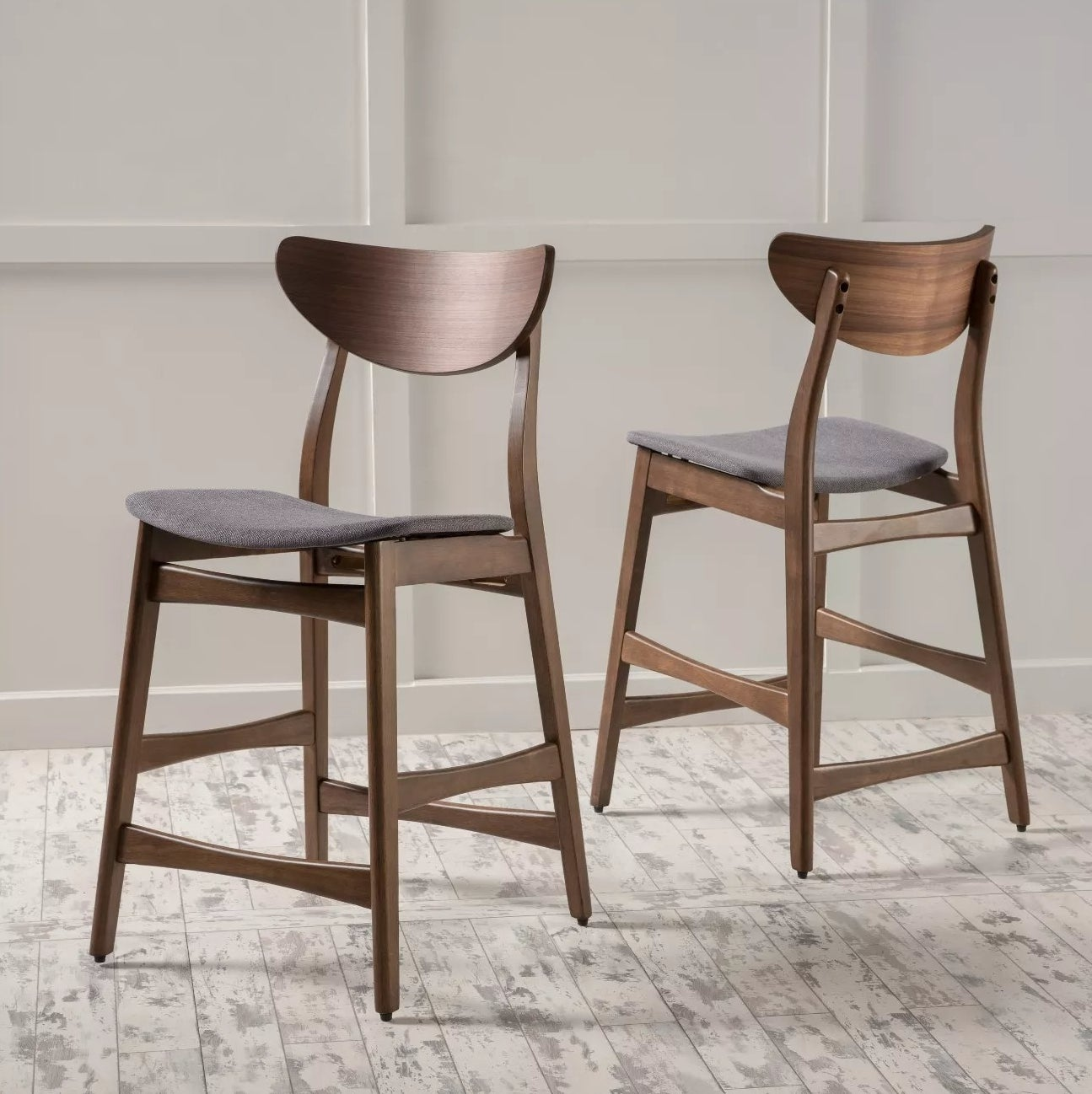 A pair of wood stools with dark gray, fabric-covered seats