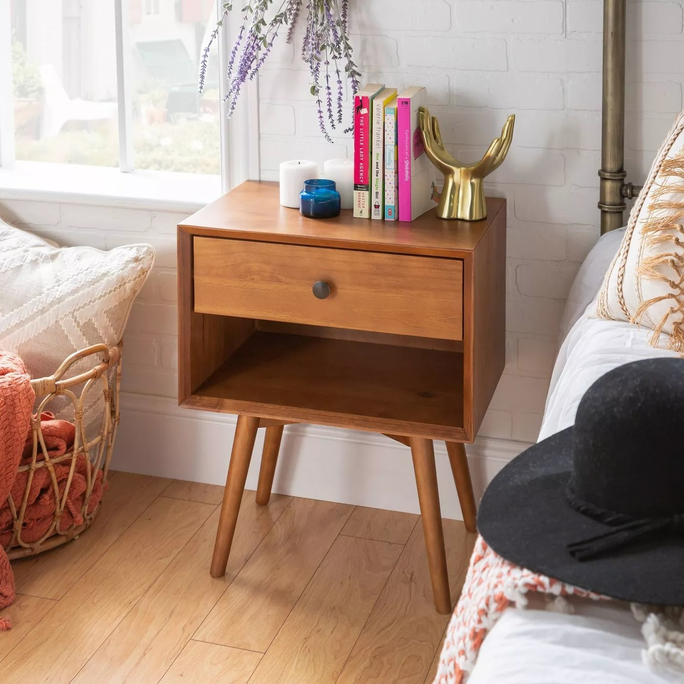 A caramel-colored nightstand with one drawer and one shelf
