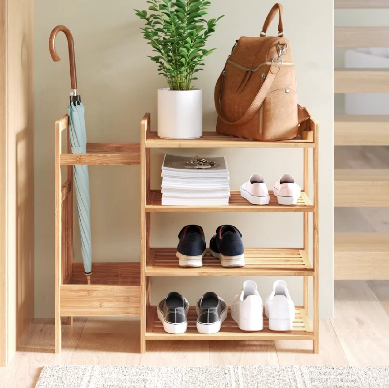 The bamboo shoe rack being used to hold shoes, an umbrella, and a purse