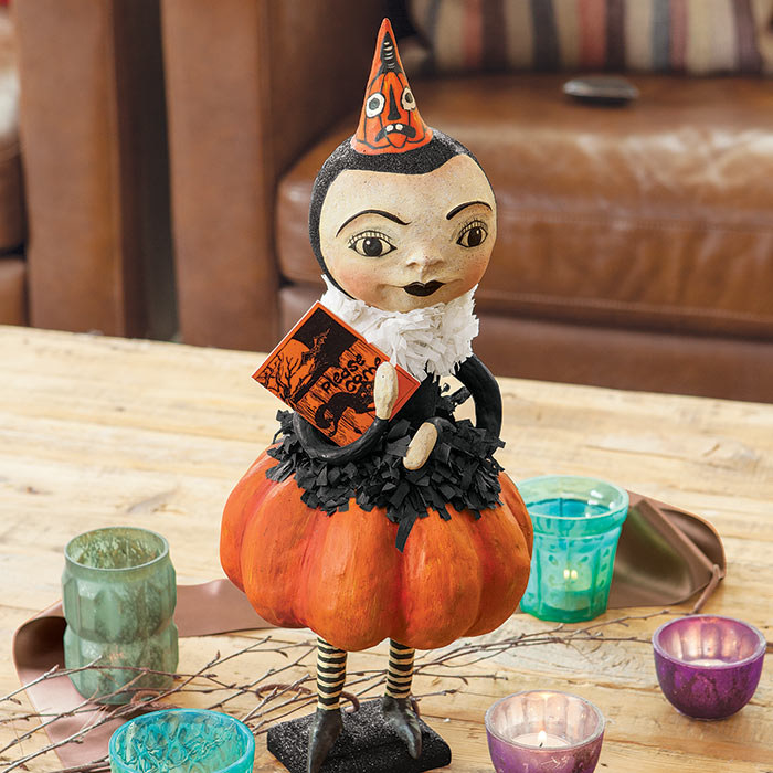 Stylized papier-mâché figurine with bulbous pumpkin pants, striped tights, black shoes, ruffled blouse and collar, spooky pumpkin face hat, and party invitation