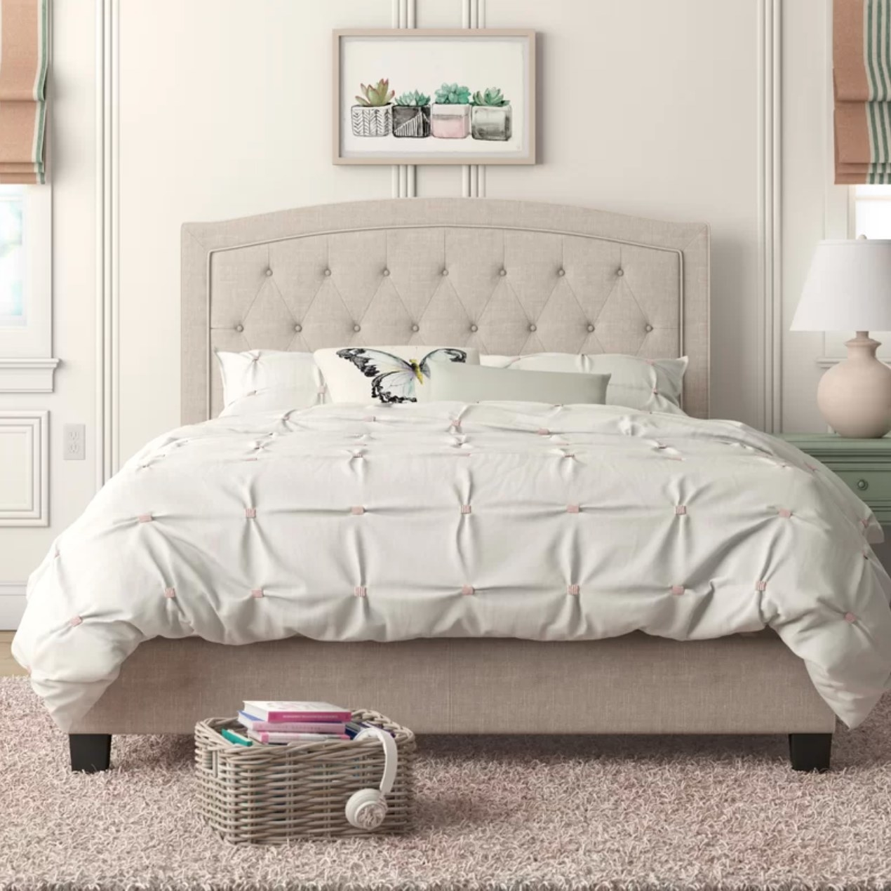The beige upholstered bed with white linens and pillows