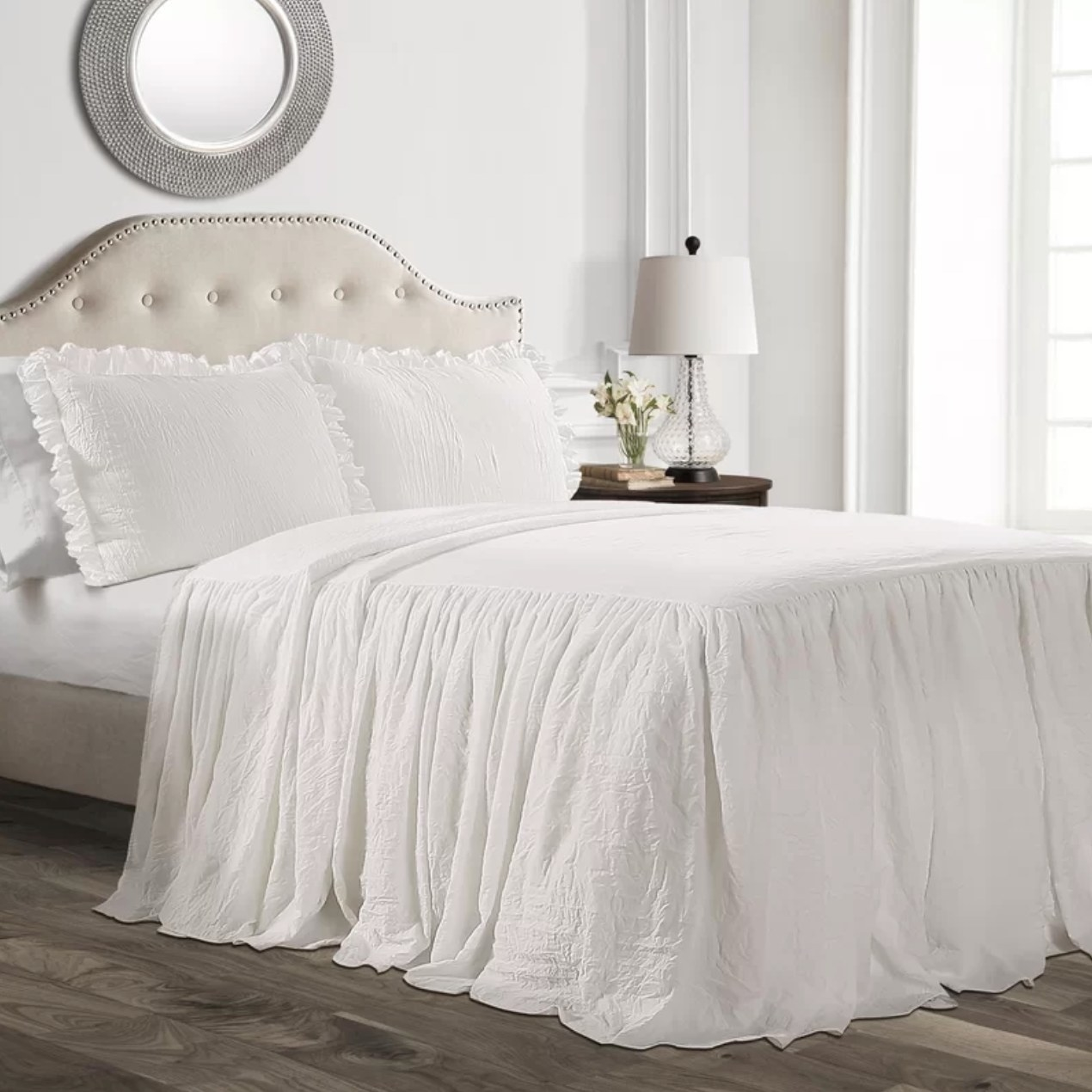 The ruffle skirt bedspread in white next to a side table with a lamp and flowers