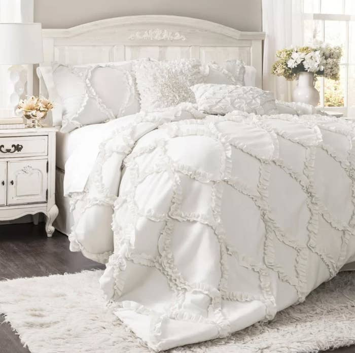 The white comforter on a bed next to two side tables with flowers