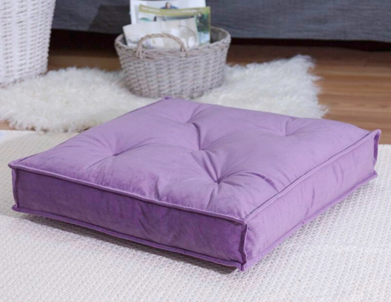 The purple floor pillow sitting atop an off-white rug