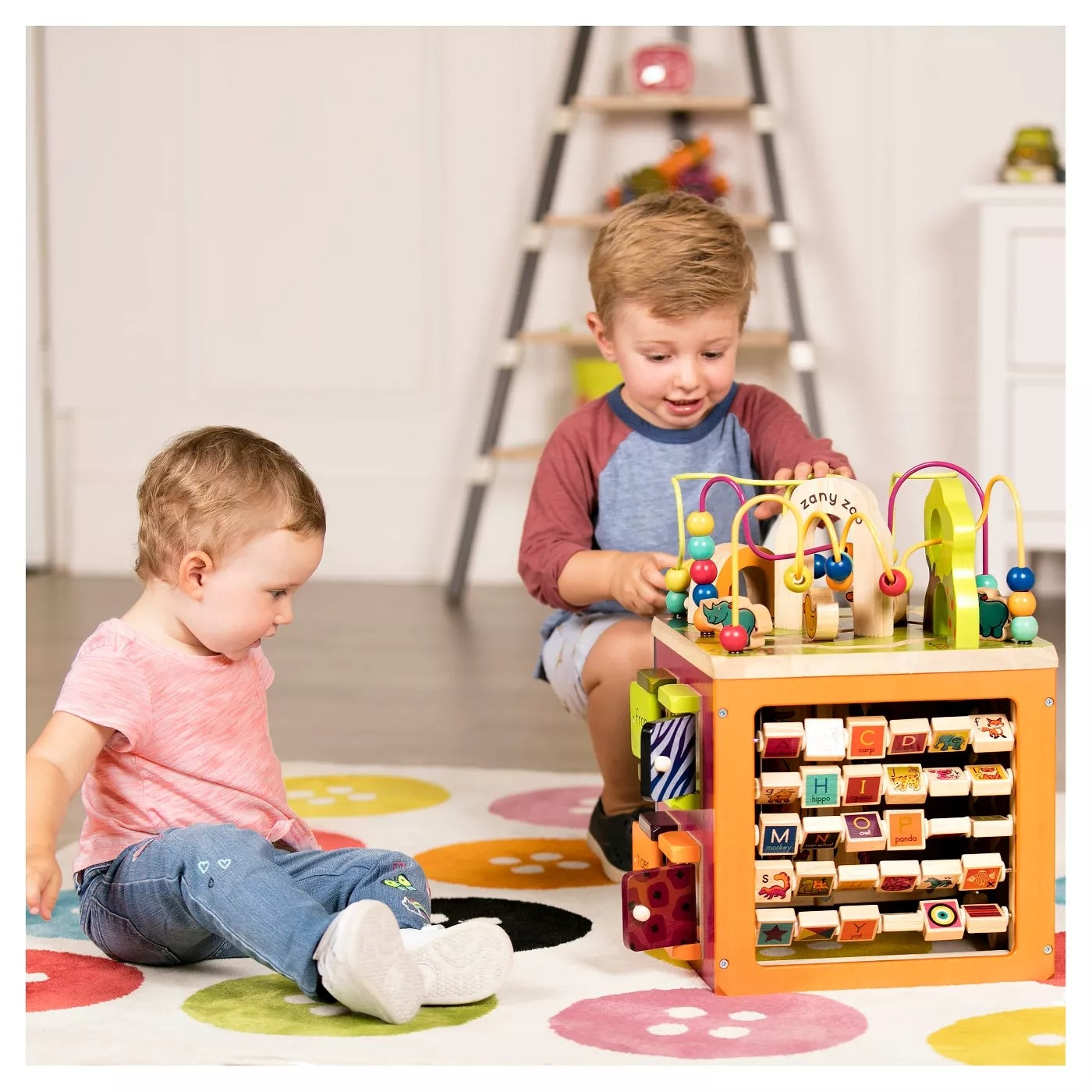 Two children playing with a cube that has different activities built into each side