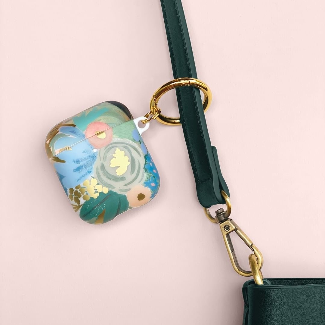 The square case with rounded edges with a blue, grey, green, and gold floral pattern and a gold ring attached to a strap of a purse.