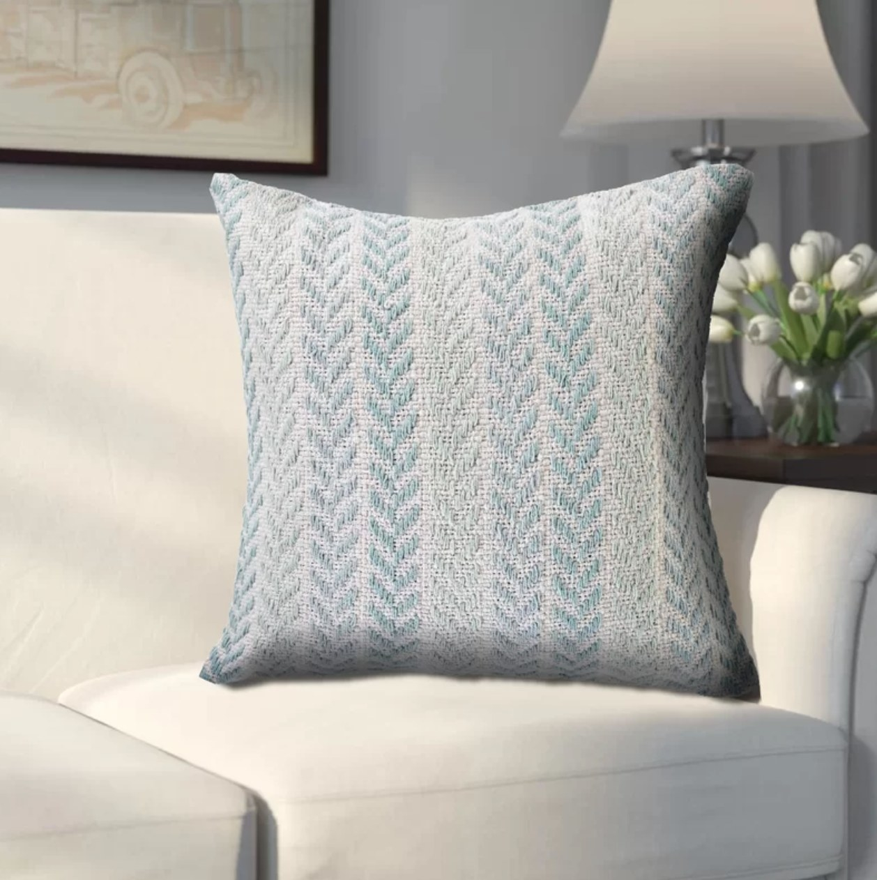 The square pillow in turquoise on a white couch