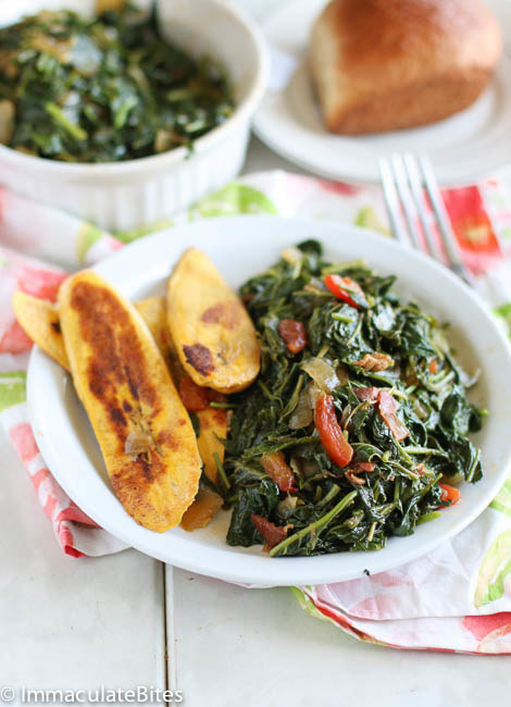 A plate of steamed leafy vegetables known as callaloo with a side of pan-fried plantains.