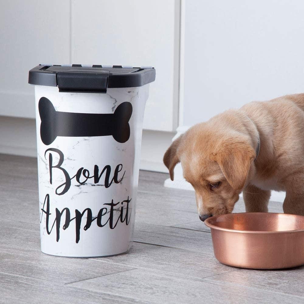A puppy beside the pet food bin
