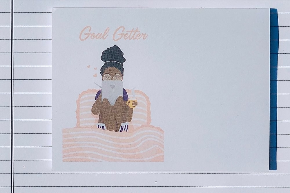"Rectangular sticky note pad with an illustration of a girl working and holding a mug on a couch with the words ""Goal Getter"" above it."