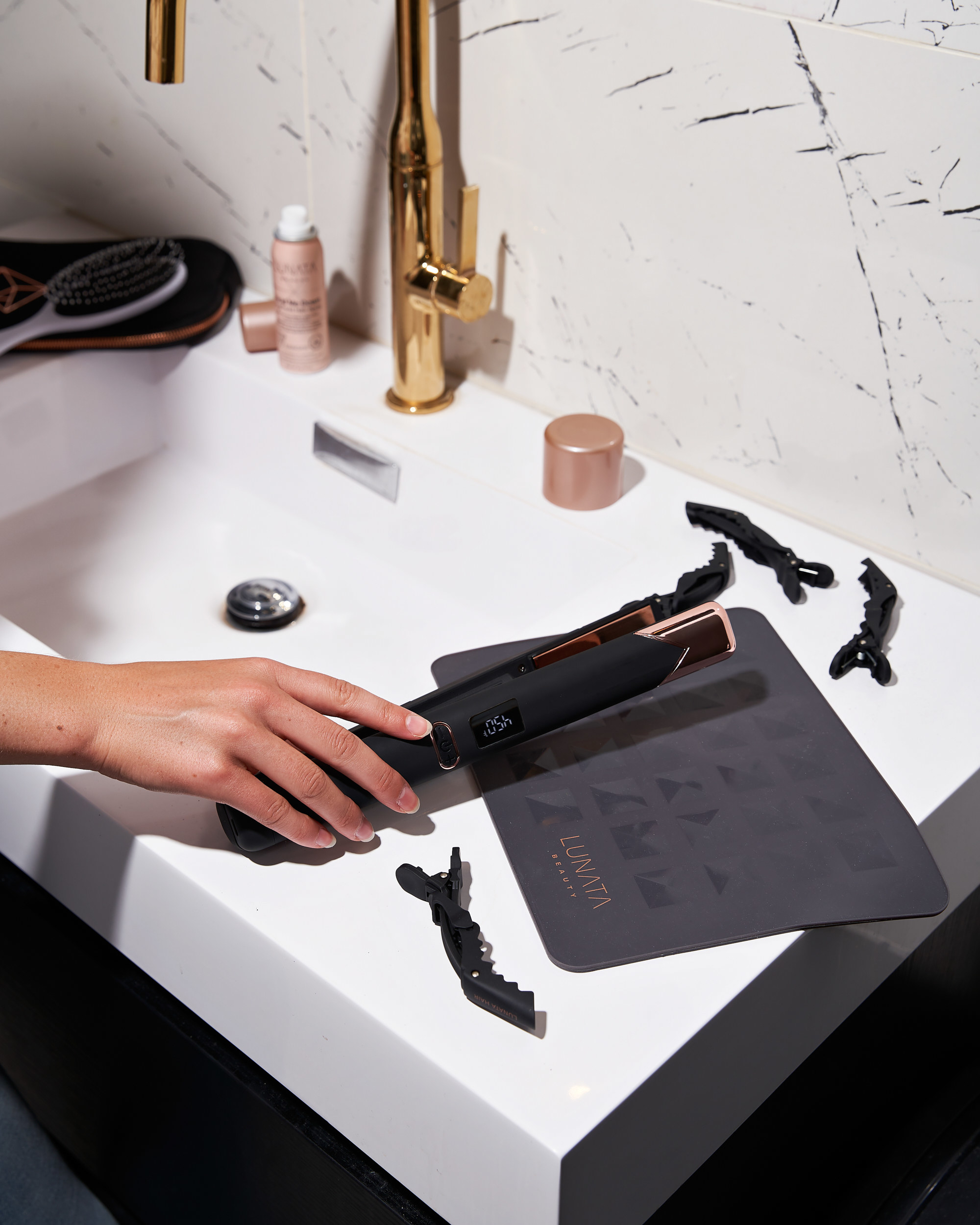 Manicured hand holds black Lunata Flat Iron Styler Plus + over a white sink