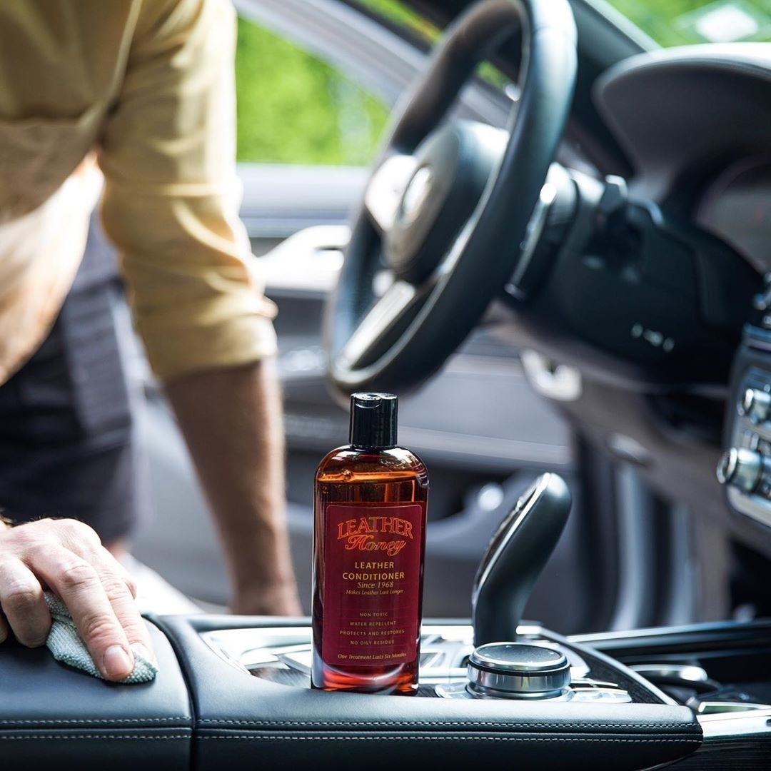 A bottle of the product inside of a car with a person rubbing the console