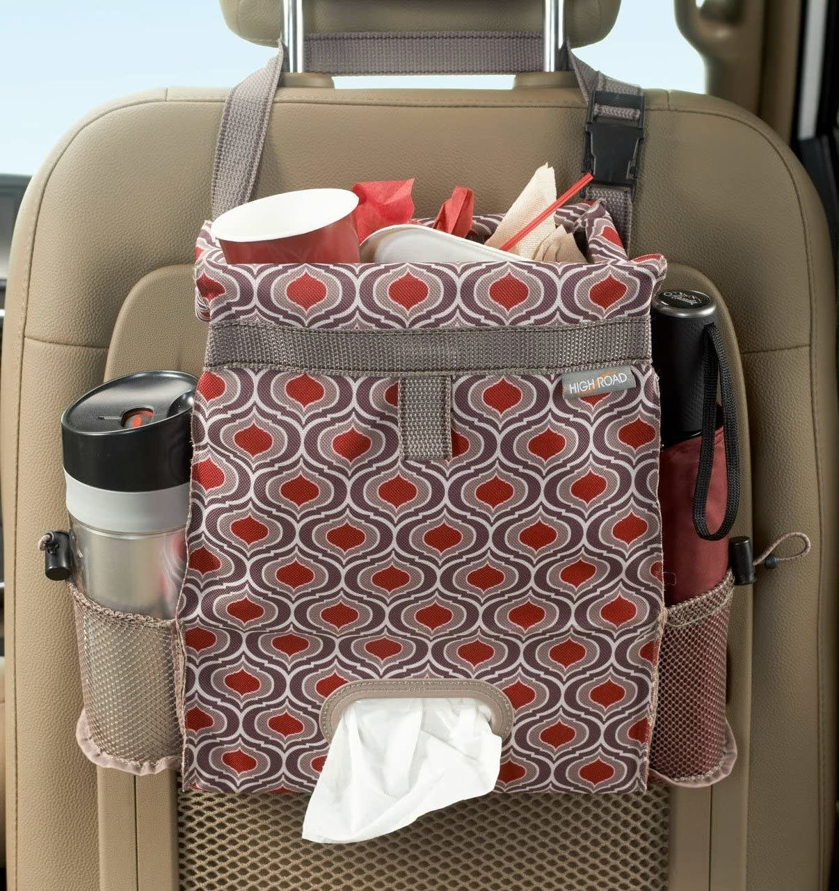 red abstract pattern organizer that goes on the back of the seat that holds tissues, trash, and water bottles